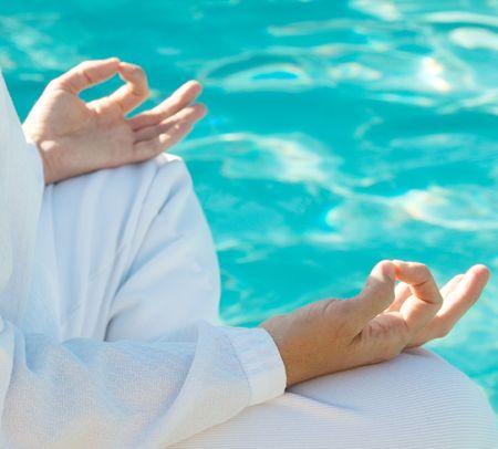 Hands in meditation mudra above water, shallow depth of field, focus on front hand Reklamní fotografie