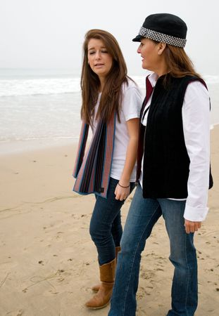 Unhappy teen girl pouring her heart out to her mom while walking along the beach on a foggy day Stock Photo - 5430478