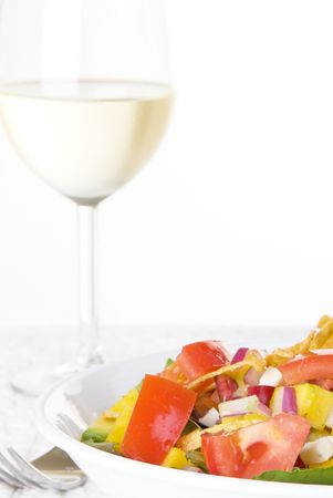sauvignon blanc: Salad with mango salsa and glass of wine. Shallow depth of field with focus on salad.