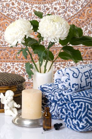 Spa towels, chrysanthemum flowers, scented oil, a basket, and an angel on patterned background