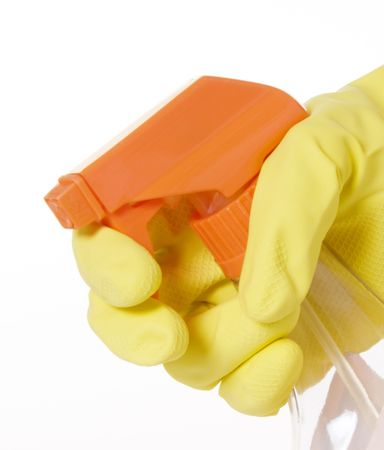 Spray bottle with orange nozzle and trigger being held by latex gloved hand