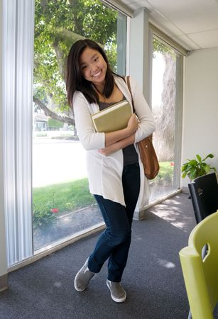 Sweet teen student carrying a book and book bag Stock Photo - 5439222