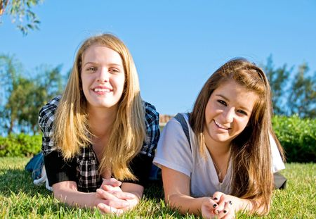 Teen girl friends hanging out in the grass at a park photo