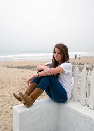Pretty teen girl peacefully gazing at the ocean