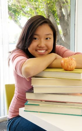 Beautiful teenage girl in classroom resting on a stack of books photo