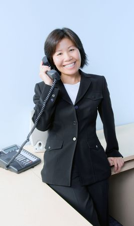 contact center: Pretty businesswoman answering the telephone Stock Photo