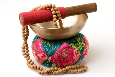 Tibetan singing bowl on quilted pad with sandalwood prayer beads