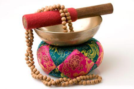Tibetan singing bowl on quilted pad with sandalwood prayer beads
