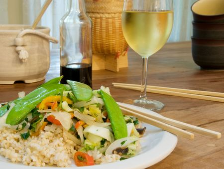 Fresh vegetable stir fry on brown rice with glass of chardonnay