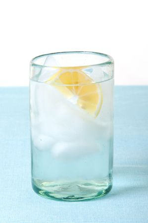 lemon wedge: Glass of ice water with lemon wedge on blue tablecloth