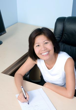 person writing: Smiling busisesswoman in her office working with pen in hand