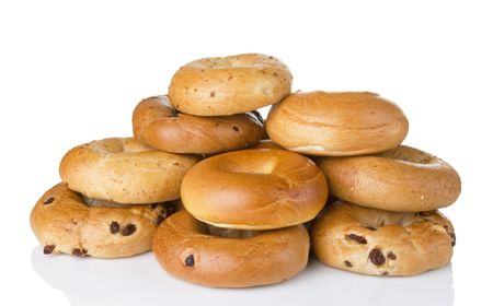 Stack of a dozen golden brown bagels in a variety of flavors