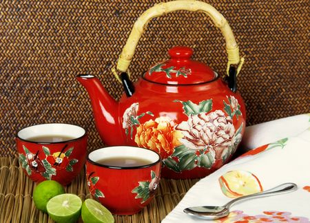 Red flowered teapot with cups of tea and lime wedges Stock fotó