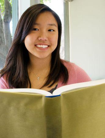 Pretty teen girl in a classroom with an open book Reklamní fotografie
