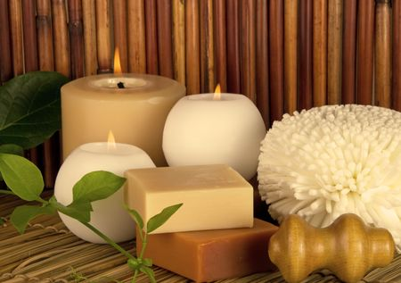 Spa items with burning candles and a green vine