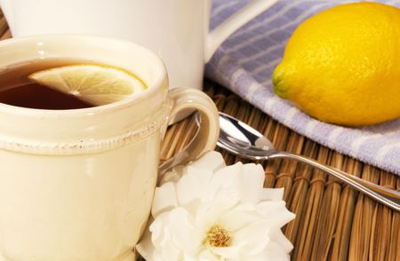 Cup of freshly brewed tea and lemon served with a white rose from the garden, focus on front rim of cup Stock fotó