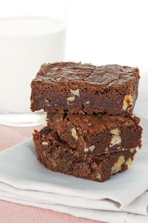 Freshly baked brownies on a napkin with glass of milk Stock Photo