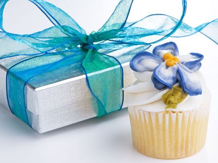 Mini cupcake and silver gift box with blue ribbon photo