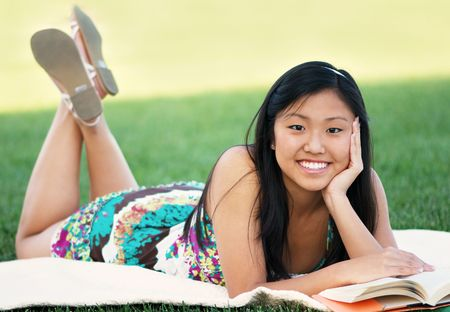 Teenage girl enjoying reading on a blanket at the park photo