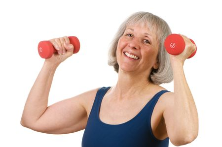 strong: Healthy senior woman in her sixties lifting hand weights with great spirit and cheer Stock Photo