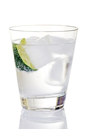 Glass of gin and tonic with ice cubes, lime wedge Stock Photo