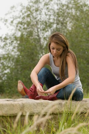 Pretty teen girl in outdoor setting looking down photo