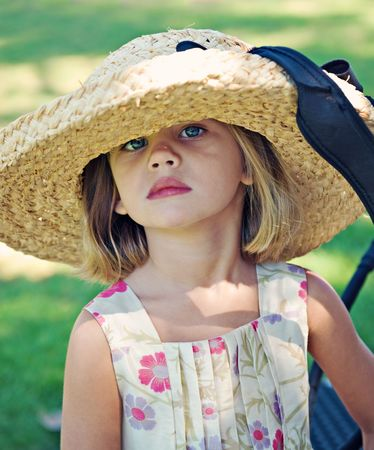Girl age 4 wearing large straw hat and flowered dress outdoors