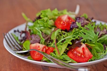 Ensalada de hojas verdes y tomate en tabla rústico, teca Foto de archivo - 9032651