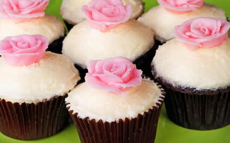 Cupcakes with white frosting and pink rose on green plate