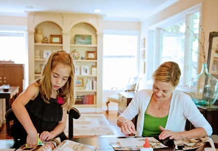to cut: Mother and daughter pasting a collage together in their family room at home Stock Photo