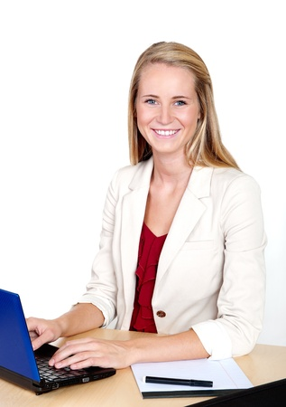 european ethnicity: Pretty young businesswoman with laptop computer at desk smiling