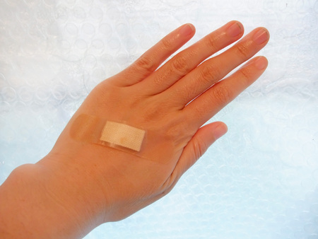 Hand with adhesive bandage