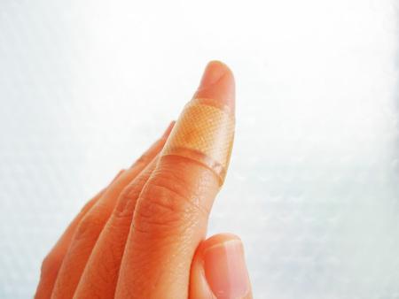 Finger with adhesive bandage
