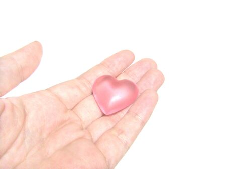 A glass heart is riding on the palm of hand