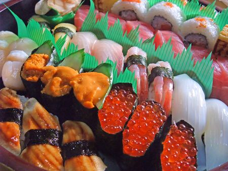 There are many different types of sushi lined up Banco de Imagens