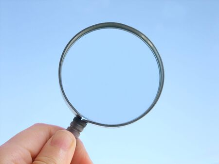 Magnifying glass held up against the sky