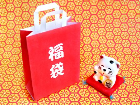 There is a lucky bag and a small beckoning cat Stockfoto