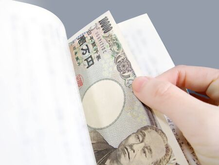 Japanese banknotes sandwiched between books Banco de Imagens