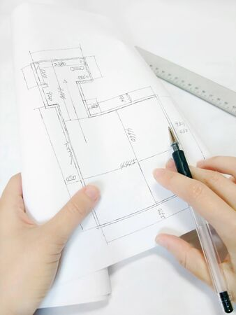 Hand holding house blueprint and pen Banco de Imagens