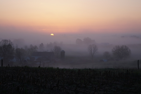 early morning fog over farm in the country Stock Photo