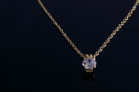 Gold diamond necklace on black background.