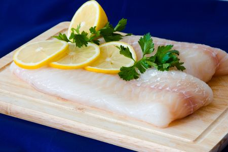Raw fish fillet with punch and lemons Stock Photo - 5536845