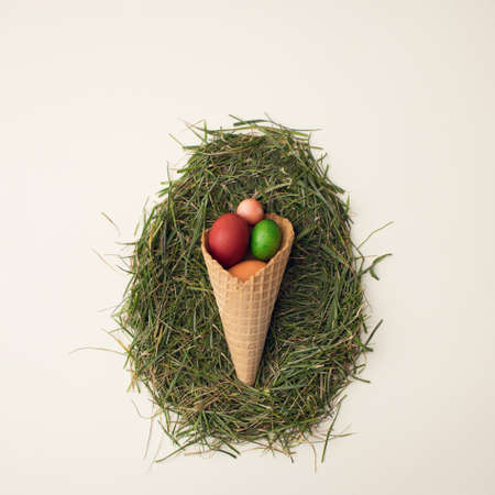 Easter colorful eggs in brown cornet on grass. Beige background. Flat lay.
