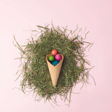 Easter colorful eggs in brown cornet on grass.
