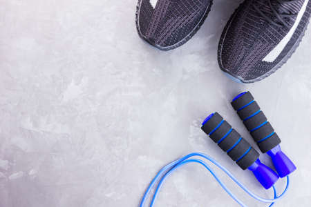 Fitness concept with black sneakers and jump rope. Sports equipment on a gray background. Healthy lifestyle concept. Top view