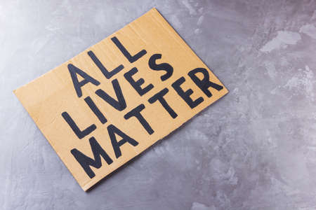 """ALL LIVES MATTER. Anti racism concept on a gray background. Equal symbol. Inscription on cardboard """"All lives matter"""". Copy space. Top view"""