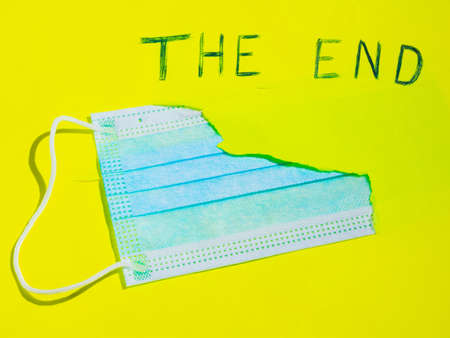 Surgical mask in a paper hole. COVID-19 protection Concept. Protective face mask and a torn yellow paper. Inscription