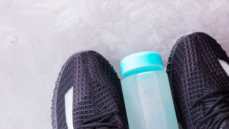 Fitness concept with sneakers and bottle of water. Sports equipment on a gray background. Healthy lifestyle concept. Copy space. Top view