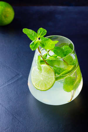 Cocktail mojito with lime and mint in glass. One glass of mojito on a dark background. Refreshing mint cocktail with lime. Infused water Zdjęcie Seryjne