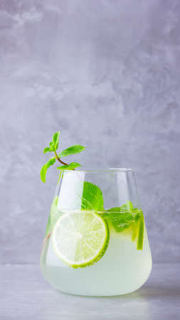 Mojito cocktail with lime and mint in glass. Mojito in glass on a gray background. Refreshing mint cocktail with lime. Infused water. Copy space